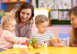 Children toddlers with kindergarten teacher is playing