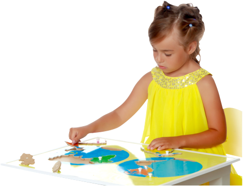 A little girl in kindergarten sits at a table and playing with puzzle