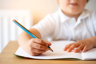 Blurry face of Kid holding pencil doing home work