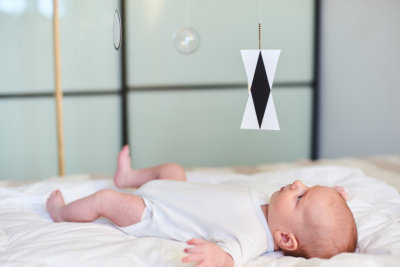 Adorable baby boy infant in white onesies, lying in bed