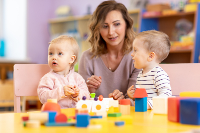 Children toddlers with kindergarten teacher is playing with montessori material. Learning through experience concept, gross and fine motor skills