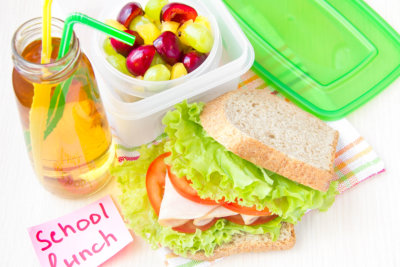 packed lunch for your child in school, box with a healthy sandwich and fruit salad and apple juice in the bottle for drinking