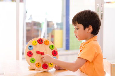 Little boy learning time with clock toy
