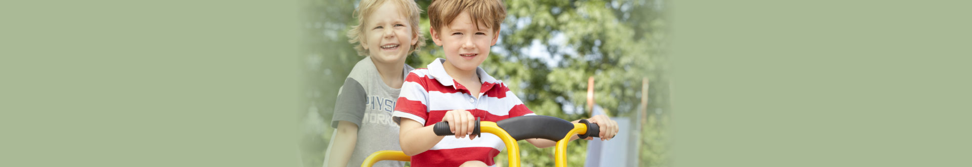 two boys riding a tricycle